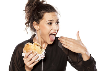 Young woman with spicy sandwich and burning tongue