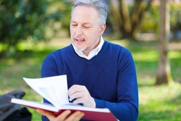 Senior man reading a book at the park