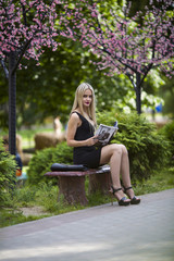 young girl reads the magazine sitting on a bench in park