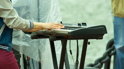 Musician plays a synthesizer, shooting side