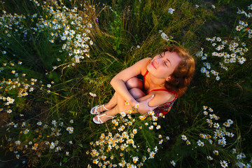 Young woman sitting in meadow with daisies top view