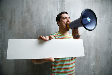 man yells into a megaphone and shows white plate on gray backgro