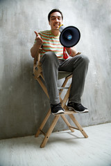 man sitting on a high chair, holding a megaphone and cute smiles