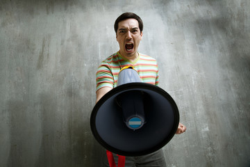 man holding a megaphone and shouting at him, against a gray text