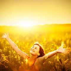 Woman raising arms enjoying sunlight in canola field