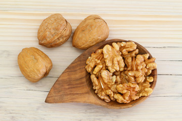 Walnuts with and without shell on wooden background
