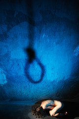Naked woman and shadow of a noose. Rape, violence, suicide.