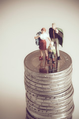 Family on pile of coins. Budget concept. Macro with retro effect