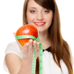 Diet. Girl holding apple with measure tape