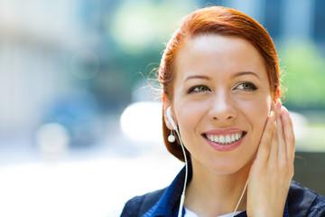 Closeup portrait woman walking on street listening to music