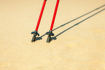 Nordic walking. Red sticks on the sandy beach