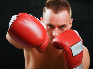 Young boxer man isolated on black background