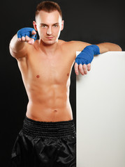 Young boxer man standing near board and pointing at you,