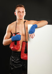 Young boxer man standing near board , isolated on black