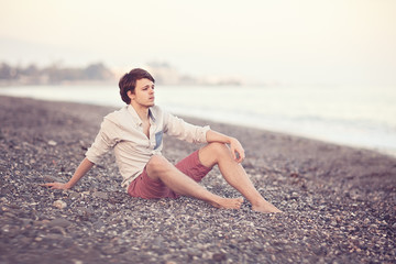 portrait of a teen sitting on the beach.soft evening light.