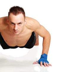 Young fitness man doing push ups on floor