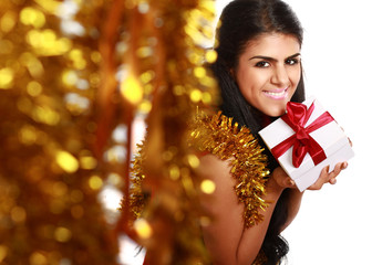 Beautiful girl with gift christmas decorated background