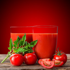 Fresh tomato drinks on wooden table.
