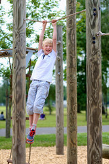 Happy school boy climbing in playground at the park