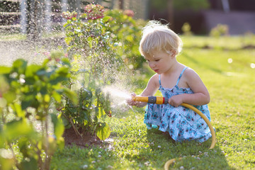Cute toddler girl watering flowers from hose in summer garden