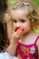 Blonde girl in summer dress eating strawberries.