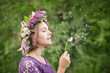 Cute girl in a wreath of lilacs blowing on a dandelion