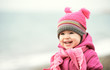 Happy baby girl in  pink hat and scarf laughs