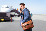 Airport business man on smartphone by plane