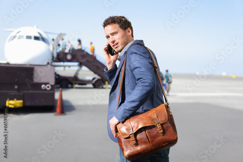 Leinwanddruck Bild Airport business man on smartphone by plane