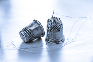 Sewing thimbles and needle with thread