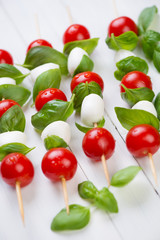 Skewers with mozzarella balls, red tomatoes and basil leaves