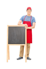 Man in apron standing behind a blackboard