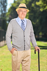 Senior gentleman with a cane posing in the park