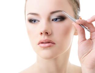 Beautiful girl plucking eyebrows with tweezers over white
