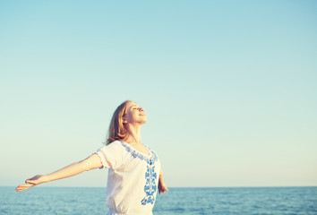 happy young woman open her arms to the sky and sea
