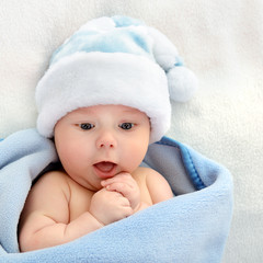 christmas cute baby boy, beautiful infant in Santa's hat and blu