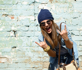 portrait of beautiful cool girl gesturing in hat and sunglasses