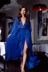 Sexy woman in blue long evening dress of silk with a slit