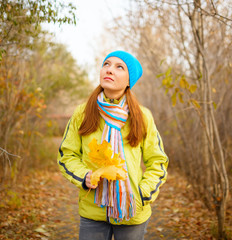 Young woman walking in the fall season. Autumn outdoor portrait