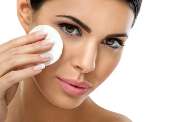 care woman removing face makeup with cotton pad