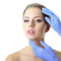 Beauty treatment of the young beautiful female face, doctor's ha