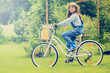Spring Cycling -  girl with bicycle in spring garden