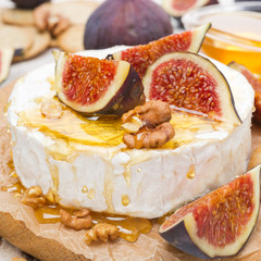 Camembert cheese with honey, figs and crackers on wooden board