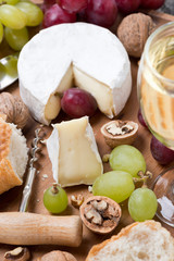 Camembert, glass of white wine, grapes and fresh baguette