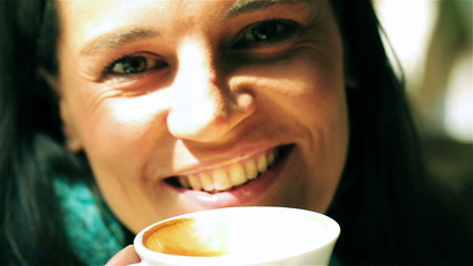 Woman drinking coffee and looking to the camera, closeup, steady