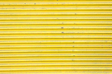 Yellow corrugated metal sheet slide door as background