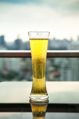 Glass of beer with High Building in Business District Background