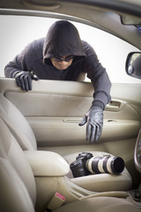 thief stealing camera  from car