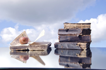 old  books and rotten apple on mirror concept