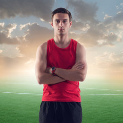 Athletic man, sportsman on background green football soccer